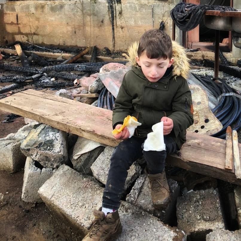 Junge in den Trümmern des abgebrannten Hauses